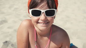Teenager girl in sunglasses smile. Into camera on the beach stock video footage
