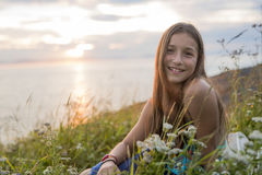 Teenager girl at sunset on the side of the sea Stock Images
