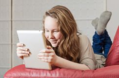Teenager girl with tablet computer. Smiling teenager girl lying on sofa with tablet computer Royalty Free Stock Photography