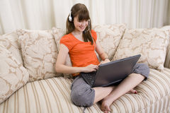 A teenager girl talking with a headset on a laptop Royalty Free Stock Photos