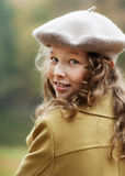 Teenager girl turning around. Portrait of blond teenager girl in grey beret in an autumn park Royalty Free Stock Photo