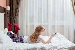 Teenager girl with TV remote Royalty Free Stock Images