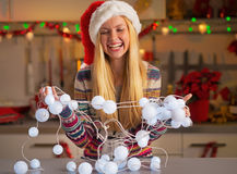 Teenager girl untangling christmas lights Royalty Free Stock Images