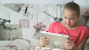 Teenager girl uses a digital tablet on the bed stock video