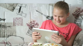 Teenager girl uses a digital tablet on the bed. A smiling teenager girl uses a digital tablet computer on the bed stock footage