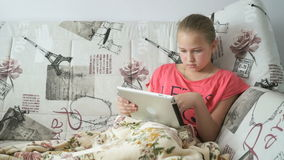 Teenager girl uses a digital tablet on the bed. A smiling teenager girl uses a digital tablet computer on the bed stock video
