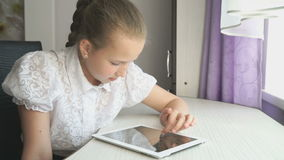 Teenager girl uses a digital tablet at the desk. Teenager girl smiles while uses a digital tablet computer at the desk at home stock footage