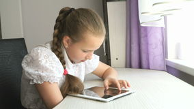 Teenager girl uses a digital tablet at the desk. Teenager girl smiles while uses a digital tablet computer at the desk at home stock video footage