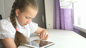 Teenager girl uses a digital tablet at the desk. Teenager girl smiles while uses a digital tablet computer at the desk at home stock video