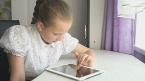 Teenager girl uses a digital tablet at the desk stock video