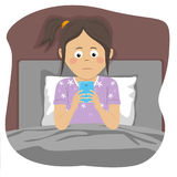 Teenager girl uses smartphone sitting in bed at night Stock Images