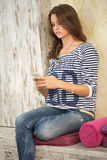 Teenager girl using her smart phone Stock Images