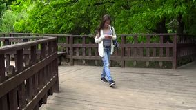 Teenager girl using mobile phone on the wooden bridge. Young teen texting message on smartphone walking. Motion camera