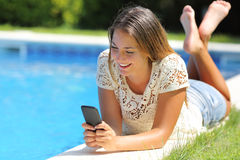 Teenager girl using a smart phone resting on a pool side. With a blue water background Stock Image