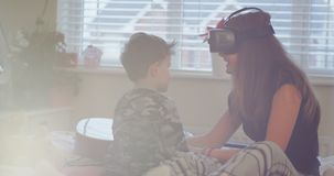 Teenager girl while using a VR playing on the bed with her small brother , happy they spend a funny time together stock video footage