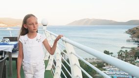 Teenager girl walking on outdoor terrace with sea and mountain landscape. Happy girl touching handrail on summer balcony. In resort with sea and beach view stock video