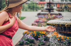 Teenager girl washes hand in fountain royalty free stock photography