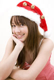 Teenager girl wearing a Christmas hat. Closeup of a teenager girl wearing a Christmas hat with fur and bells. White background Royalty Free Stock Photos