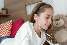Teenager girl wearing earphone playing on tablet Royalty Free Stock Photography
