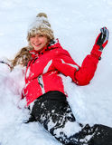 Teenager girl wearing winter clothes lying in deep snow . Stock Photography