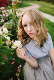 Teenager girl in wedding dress. In nature green park with rose and sunset light Royalty Free Stock Photos
