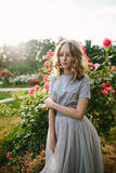 Teenager girl in wedding dress. In nature green park with rose and sunset light Royalty Free Stock Photography