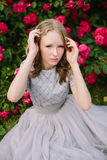 Teenager girl in wedding dress. In nature green park with rose and sunset light Royalty Free Stock Image