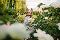 Teenager girl in wedding dress. In nature green park with rose and sunset light Stock Photo