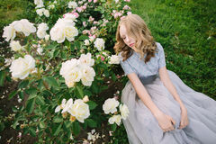 Teenager girl in wedding dress. In nature green park with rose and sunset light Stock Photography