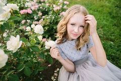 Teenager girl in wedding dress. In nature green park with rose and sunset light Stock Images