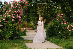 Teenager girl in wedding dress. In nature green park with rose and sunset light Stock Photos