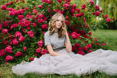 Teenager girl in wedding dress. In nature green park with rose and sunset light Royalty Free Stock Photo