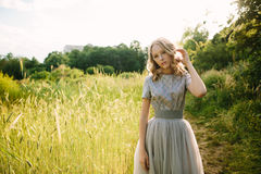Teenager girl in wedding dress. In nature green  park and sunset light Royalty Free Stock Images