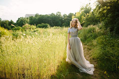 Teenager girl in wedding dress. In nature green  park and sunset light Stock Photo