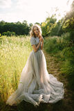 Teenager girl in wedding dress. In nature green  park and sunset light Royalty Free Stock Photography