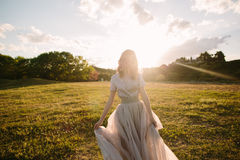 Teenager girl in wedding dress. In nature green park with and sunset light Royalty Free Stock Photo
