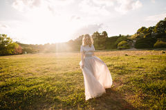 Teenager girl in wedding dress. In nature green park with and sunset light Royalty Free Stock Images