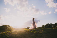 Teenager girl in wedding dress. In nature green park with and sunset light Stock Photo