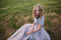 Teenager girl in wedding dress. In nature green park with and sunset light Stock Images