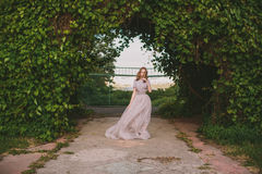 Teenager girl in wedding dress. In nature green park with and sunset light Stock Photography