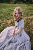 Teenager girl in wedding dress. In nature green park with and sunset light Stock Photos