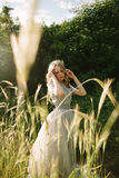 Teenager girl in wedding dress. In nature green  park and sunset light Royalty Free Stock Image