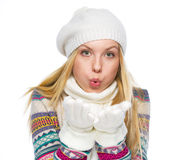 Teenager girl in winter clothes blowing snow from hands Royalty Free Stock Images