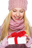 Teenager girl in winter hat and scarf with presenting box Royalty Free Stock Photography