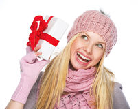 Teenager girl in winter hat and scarf shaking presenting box. Smiling teenager girl in winter hat and scarf shaking presenting box Royalty Free Stock Images