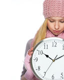 Teenager girl in winter hat and scarf showing clock Royalty Free Stock Photo