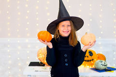 Teenager girl in witch costume posing with pumpkins Stock Photo
