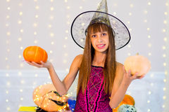 Teenager girl in witch costume posing with pumpkins Stock Images