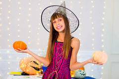 Teenager girl in witch costume posing with pumpkins Stock Image