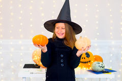 Teenager girl in witch costume posing with pumpkins Royalty Free Stock Image